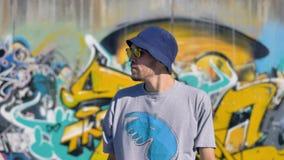 Το πορτρέτο του ενήλικου ατόμου στέκεται με ένα γκράφιτι που χρωματίζει στο υπόβαθρο και που κοιτάζει γύρω απόθεμα βίντεο