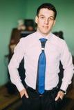 Το πορτρέτο του ευτυχούς επιχειρηματία με παραδίδει τις τσέπες που στέκονται στο δωμάτιο ξενοδοχείου στοκ φωτογραφία με δικαίωμα ελεύθερης χρήσης