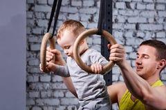 Το πορτρέτο του ευτυχούς νέου πατέρα εκπαιδεύει το μικρό γιο με τα gimnastic δαχτυλίδια ενάντια στο τουβλότοιχο στη γυμναστική Στοκ Εικόνες