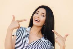 Το πορτρέτο του ευτυχούς πανέμορφου θηλυκού προτύπου δείχνει με τα πρόσθια δάχτυλα στο πρόσωπό της, διαφημίζει τα στηρίγματα για  στοκ φωτογραφία