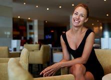 Το πορτρέτο του ευτυχούς πανέμορφου χρηματοδότη γυναικών έντυσε στα κομψά ενδύματα που θέτουν καθμένος στο εσωτερικό καφετεριών Στοκ Εικόνες