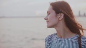 Το πορτρέτο του ευτυχούς στοχαστικού νέου ευρωπαϊκού κοριτσιού με την τρίχα που φυσά στον αέρα και η ηρεμία χαμογελούν στην παραλ φιλμ μικρού μήκους