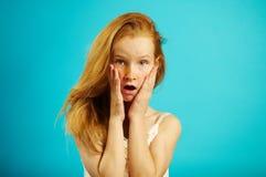 Το πορτρέτο του ζαλισμένου κοριτσιού με την κόκκινη τρίχα βάζει τα χέρια του στα μάγουλα, εκφράζει την έκπληξη και ο κλονισμός, κ στοκ εικόνα