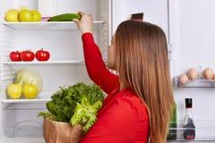 Το πορτρέτο του θηλυκού βάζει τα λαχανικά στα ράφια του ψυγείου, αγοράζει το μαρούλι, τον άνηθο και τα αγγούρια, στάσεις πίσω, πο Στοκ εικόνες με δικαίωμα ελεύθερης χρήσης