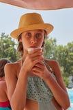 Το πορτρέτο του κοριτσιού είναι drinkig φρέσκος χυμός, θερινό βουνό landsc Στοκ Φωτογραφία