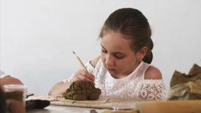 Το πορτρέτο του κοριτσιού παιδιών διαμορφώνει τα παιχνίδια από τον άργιλο φιλμ μικρού μήκους