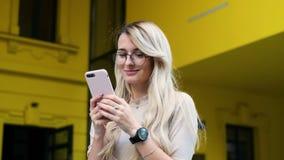 Το πορτρέτο του κοριτσιού που χρησιμοποιεί το smartphone της στο κείμενο και στέλνει τις φωτογραφίες Γυναίκα που κοιτάζει βιαστικ φιλμ μικρού μήκους