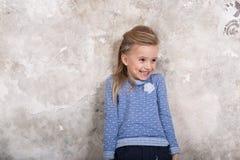 Το πορτρέτο του λίγο ελκυστικού χαμογελώντας κοριτσιού σε ένα μπλε πουλόβερ και των εσωρούχων με την τρίχα δίπλωσε στην τρίχα της στοκ φωτογραφίες με δικαίωμα ελεύθερης χρήσης