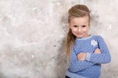 Το πορτρέτο του λίγο ελκυστικού χαμογελώντας κοριτσιού σε ένα μπλε πουλόβερ και των εσωρούχων με την τρίχα δίπλωσε στην τρίχα της στοκ φωτογραφία με δικαίωμα ελεύθερης χρήσης