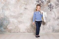 Το πορτρέτο του λίγο ελκυστικού χαμογελώντας κοριτσιού σε ένα μπλε πουλόβερ και των εσωρούχων με την τρίχα δίπλωσε στην τρίχα της στοκ εικόνα