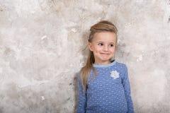 Το πορτρέτο του λίγο ελκυστικού χαμογελώντας κοριτσιού σε ένα μπλε πουλόβερ και των εσωρούχων με την τρίχα δίπλωσε στην τρίχα της στοκ φωτογραφία