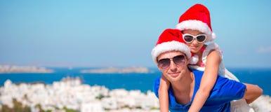 Το πορτρέτο του μικρού κοριτσιού και ο ευτυχής μπαμπάς στα καπέλα Santa απολαμβάνουν τις διακοπές Χριστουγέννων με την όμορφη άπο Στοκ Φωτογραφία