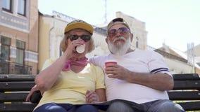Το πορτρέτο του μοντέρνου ανώτερου ζεύγους πίνει τον καφέ και τη χαλάρωση στον πάγκο στην πόλη φιλμ μικρού μήκους