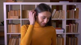 Το πορτρέτο του μοντέρνου θηλυκού δασκάλου brunette χαμογελά ευτυχώς στη κάμερα και φλερτ με το στη βιβλιοθήκη φιλμ μικρού μήκους