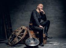 Το πορτρέτο του μουσικού που ντύνεται στα παλαιά κελτικά ενδύματα κάθεται σε ένα ξύλινο κιβώτιο και εκτέλεση του παλαιού μαντολίν Στοκ Φωτογραφίες