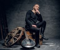 Το πορτρέτο του μουσικού που ντύνεται στα παλαιά κελτικά ενδύματα κάθεται σε ένα ξύλινο κιβώτιο και εκτέλεση του παλαιού μαντολίν Στοκ εικόνες με δικαίωμα ελεύθερης χρήσης