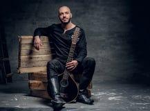 Το πορτρέτο του μουσικού που ντύνεται στα παλαιά κελτικά ενδύματα κάθεται σε ένα ξύλινο κιβώτιο και εκτέλεση του παλαιού μαντολίν Στοκ Φωτογραφία
