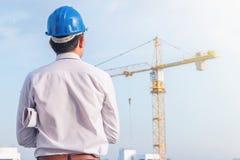 Το πορτρέτο του μπλε κράνους ασφάλειας ένδυσης μηχανικών και κρατά το σχεδιάγραμμα με την υποχρέωση στο εργοτάξιο οικοδομής με το στοκ φωτογραφίες με δικαίωμα ελεύθερης χρήσης