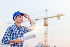 Το πορτρέτο του μπλε κράνους ασφάλειας ένδυσης μηχανικών και κρατά το σχεδιάγραμμα με την υποχρέωση στο εργοτάξιο οικοδομής με το στοκ φωτογραφίες