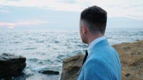 Το πορτρέτο του νέου ελκυστικού επιχειρησιακού ατόμου ή του νεόνυμφου στέκεται στην ακροθαλασσιά με τους βράχους και το όμορφο ηλ απόθεμα βίντεο