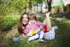 Το πορτρέτο του νέου ελκυστικού κοριτσιού με το παιδί με τα λακκάκια χαμογελά Στοκ φωτογραφία με δικαίωμα ελεύθερης χρήσης