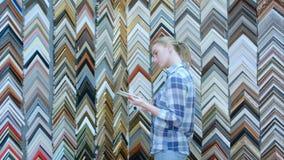Το πορτρέτο του νέου θηλυκού πελάτη που ψάχνει ένα πλαίσιο, που κρατά τα κομμάτια παραδίδει μέσα το ειδικό κατάστημα Στοκ φωτογραφίες με δικαίωμα ελεύθερης χρήσης