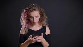Το πορτρέτο του νέου καυκάσιου κοριτσιού με τη ρόδινη προσοχή τρίχας στο smartphone της παίρνει σοβαρά διασκεδασμένο στο μαύρο υπ απόθεμα βίντεο