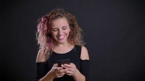Το πορτρέτο του νέου καυκάσιου κοριτσιού με τη ρόδινη προσοχή τρίχας στο smartphone της παίρνει έκπληκτο και χαρούμενο στο Μαύρο απόθεμα βίντεο