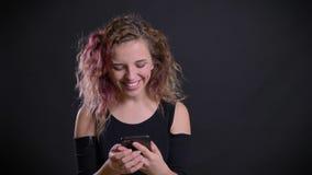 Το πορτρέτο του νέου καυκάσιου κοριτσιού με τη ρόδινη προσοχή τρίχας στο smartphone της παίρνει έκπληκτο και πολύ ευτυχές στο Μαύ απόθεμα βίντεο