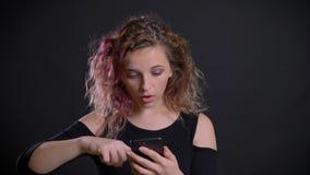 Το πορτρέτο του νέου καυκάσιου κοριτσιού με τη ρόδινη προσοχή τρίχας στο smartphone της παίρνει έκπληκτο και στο Μαύρο απόθεμα βίντεο
