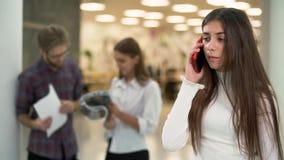Το πορτρέτο του νέου κοριτσιού ανησύχησε την ομιλία τηλεφωνικώς στη θέση εργασίας στο υπόβαθρο των κουβεντιάζοντας ανθρώπων απόθεμα βίντεο