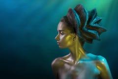 Το πορτρέτο του νέου κοριτσιού με μια εμπροσθοφυλακή hairstyle και λάμπει σύνθεση στους κίτρινος-μπλε τόνους σε ένα μπλε υπόβαθρο στοκ φωτογραφία με δικαίωμα ελεύθερης χρήσης