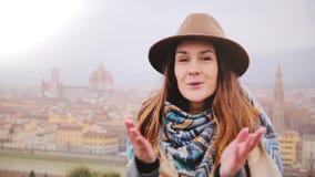 Το πορτρέτο του νέου όμορφου καυκάσιου χαμόγελου γυναικών ευτυχούς, φύσηγμα φιλά την εξέταση τη κάμερα στη Φλωρεντία μια βροχερή  απόθεμα βίντεο