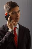 Το πορτρέτο του νεαρού άνδρα στο κοστούμι μιλά πωλεί το τηλέφωνο Στοκ Εικόνα