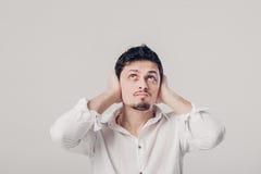Το πορτρέτο του νεαρού άνδρα στο πουκάμισο καλύπτει τα αυτιά του με hands του ag στοκ φωτογραφίες με δικαίωμα ελεύθερης χρήσης