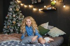 Το πορτρέτο του ξανθού μικρού κοριτσιού στο μπλε φόρεμα κάθεται σε ένα κρεβάτι στο σκοτεινό δωμάτιο Χριστουγέννων Στοκ Εικόνες