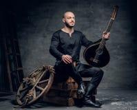 Το πορτρέτο του παραδοσιακού λαϊκού μουσικού που ντύνεται στα εκλεκτής ποιότητας κελτικά ενδύματα κάθεται σε ένα ξύλινο κιβώτιο κ Στοκ Εικόνα
