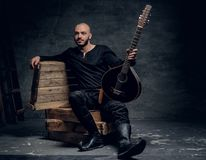 Το πορτρέτο του παραδοσιακού λαϊκού μουσικού που ντύνεται στα εκλεκτής ποιότητας κελτικά ενδύματα κάθεται σε ένα ξύλινο κιβώτιο κ Στοκ Φωτογραφία