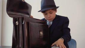 Το πορτρέτο του προϊσταμένου αγοριών παίρνει ένα πακέτο των τραπεζογραμματίων εκατό-δολαρίων από το χαρτοφύλακά του φιλμ μικρού μήκους