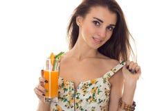Το πορτρέτο του σαγηνευτικού κοριτσιού brunette το καλοκαίρι sarafan με το floral σχέδιο πίνει το πορτοκαλί κοκτέιλ και την εξέτα Στοκ φωτογραφία με δικαίωμα ελεύθερης χρήσης