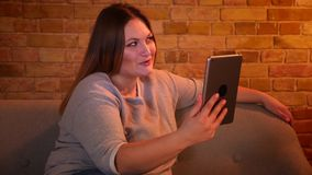 Το πορτρέτο του υπέρβαρου χαρούμενου θηλυκού προτύπου κάθεται στον καναπέ που έχει ένα βίντεο καλεί την ταμπλέτα στην άνετη εγχώρ φιλμ μικρού μήκους