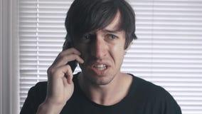 Το πορτρέτο του υ ατόμου μιλά irritatedly στο phoneon το υπόβαθρο των τυφλών απόθεμα βίντεο