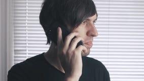 Το πορτρέτο του υ ατόμου μιλά irritatedly στο phoneon το υπόβαθρο των τυφλών φιλμ μικρού μήκους