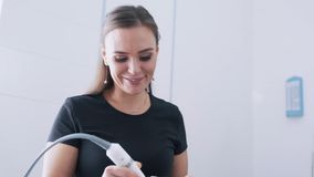 Το πορτρέτο του χαμογελώντας cosmetologist κάνει την του προσώπου διαδικασία θεραπείας σε υπομονετικό, σε αργή κίνηση απόθεμα βίντεο