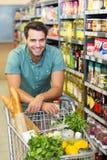 Το πορτρέτο του χαμογελώντας ατόμου αγοράζει το προϊόν με το καροτσάκι του Στοκ Φωτογραφία