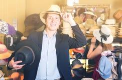 Το πορτρέτο του χαμόγελου του νέου τύπου προσπαθεί στο καπέλο κάδων στο κατάστημα Στοκ φωτογραφία με δικαίωμα ελεύθερης χρήσης