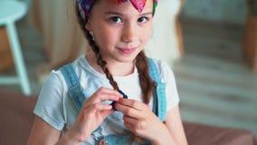Το πορτρέτο του χαριτωμένου κοριτσιού δένει την πλεξούδα με scrunchy και εξετάζει τη κάμερα, σε αργή κίνηση απόθεμα βίντεο