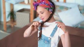 Το πορτρέτο του χαριτωμένου κοριτσιού δένει την πλεξούδα με scrunchy και εξετάζει τη κάμερα, σε αργή κίνηση φιλμ μικρού μήκους