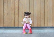 Το πορτρέτο του χαριτωμένου μικρού κοριτσιού κάθεται και αγκαλιάζοντας Teddy αντέξτε ενάντια στον ξύλινο τοίχο σανίδων στοκ φωτογραφίες με δικαίωμα ελεύθερης χρήσης