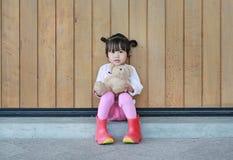 Το πορτρέτο του χαριτωμένου μικρού κοριτσιού κάθεται και αγκαλιάζοντας Teddy αντέξτε ενάντια στον ξύλινο τοίχο σανίδων στοκ εικόνες με δικαίωμα ελεύθερης χρήσης